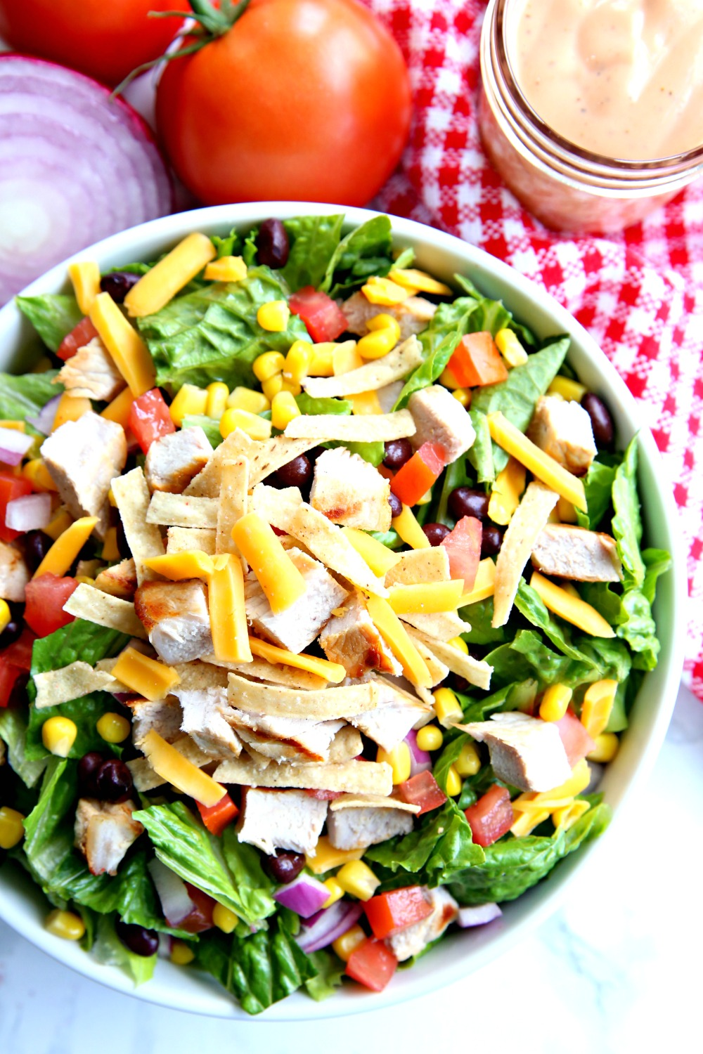 BBQ Chopped Salad topped with fresh veggies, black beans, and grilled pork chops. Serve with BBQ ranch dressing on the side.