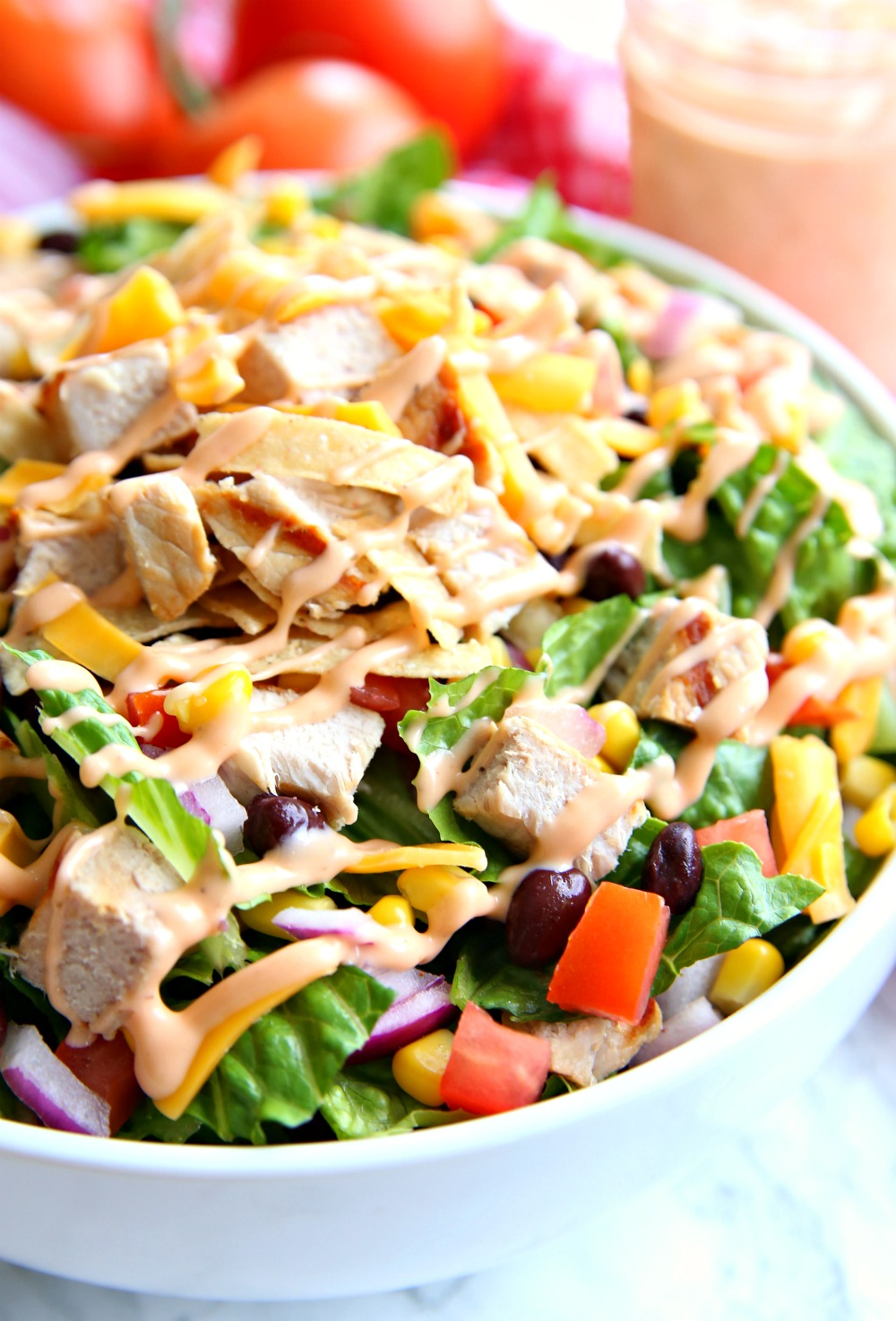 BBQ Chopped Salad in large bowl topped with black beans, fresh veggies, BBQ ranch dressing and tortilla strips.