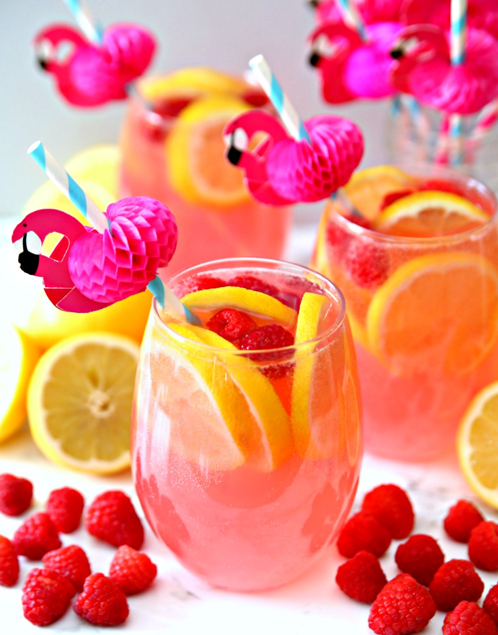 Pink Moscato Lemonade Cocktail Recipe in wine glass with frozen raspberries and lemon slices