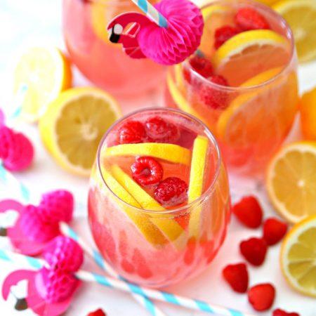 Pink Moscato Lemonade Recipe in wine glasses with lemons and raspberries