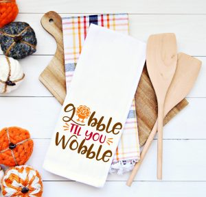 https://www.happygoluckyblog.com/wp-content/uploads/2018/10/Gobble-til-you-Wobble-on-Tea-Towel-3-300x288.jpg