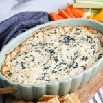 Spinach Artichoke Dip on wood board with crackers and vegetables.
