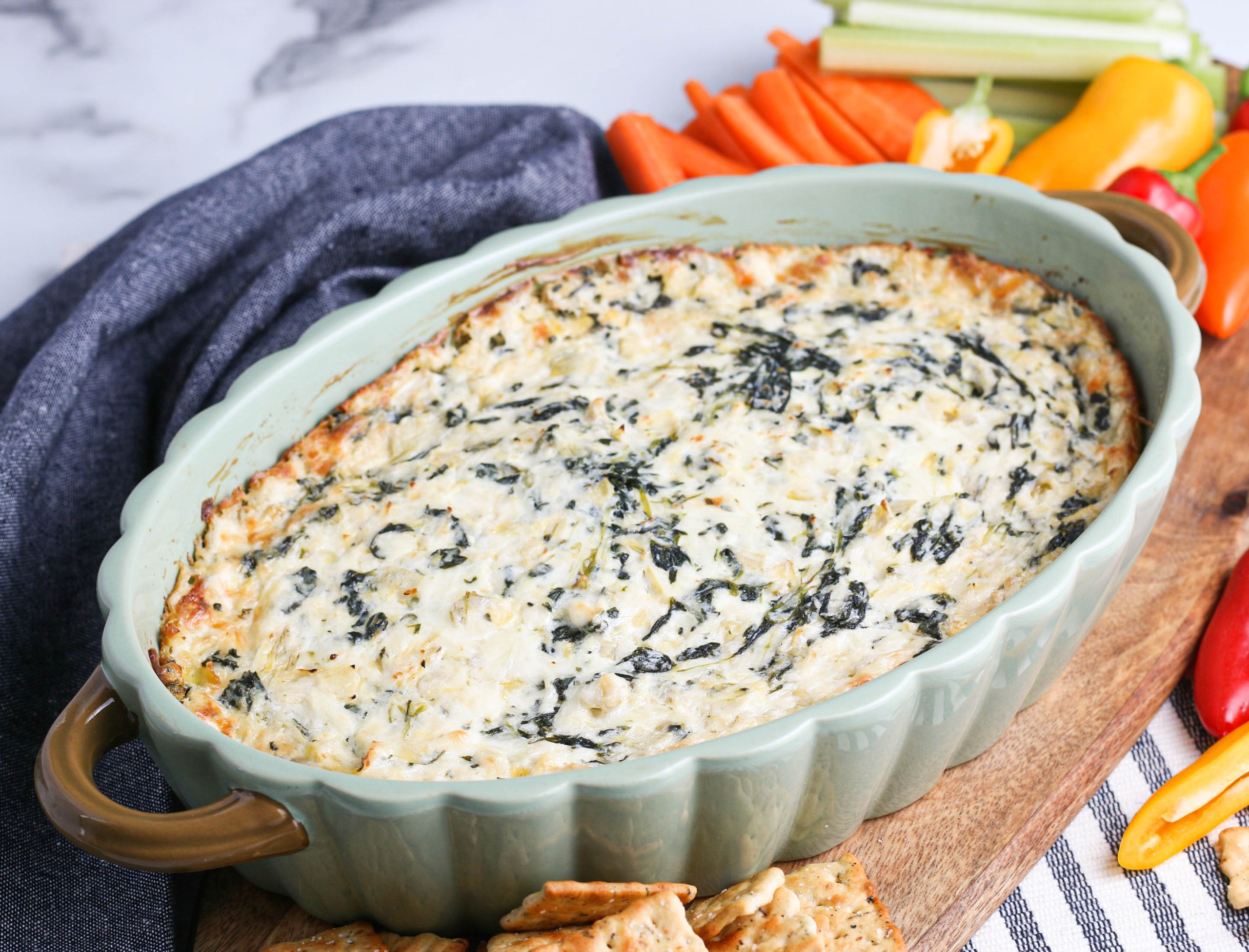 Spinach artichoke dip in light green baking dish with vegetables and crackers next to a blue napkin.