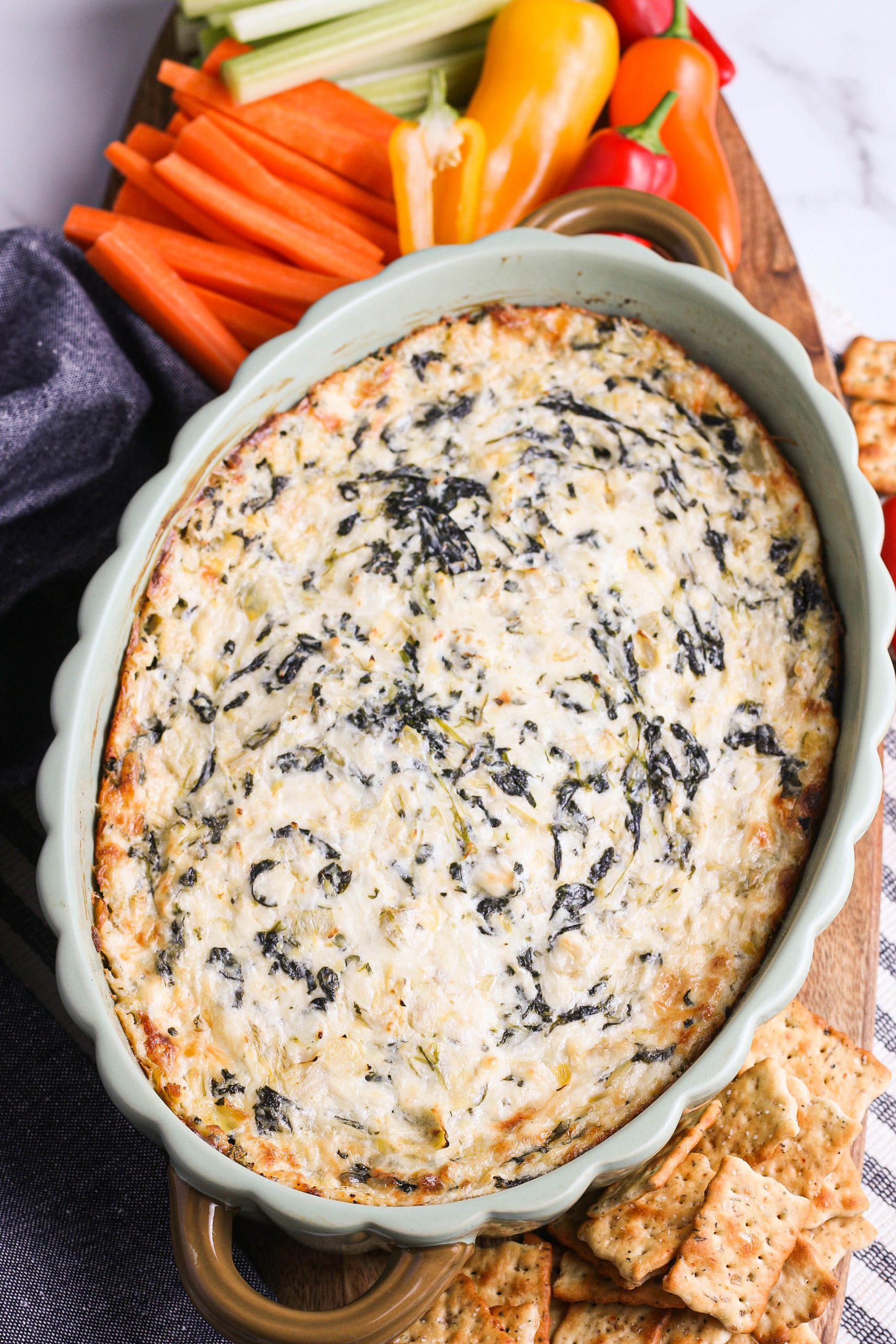 Spinach artichoke dip in light green dish with crackers, vegetables on a wood and marble background