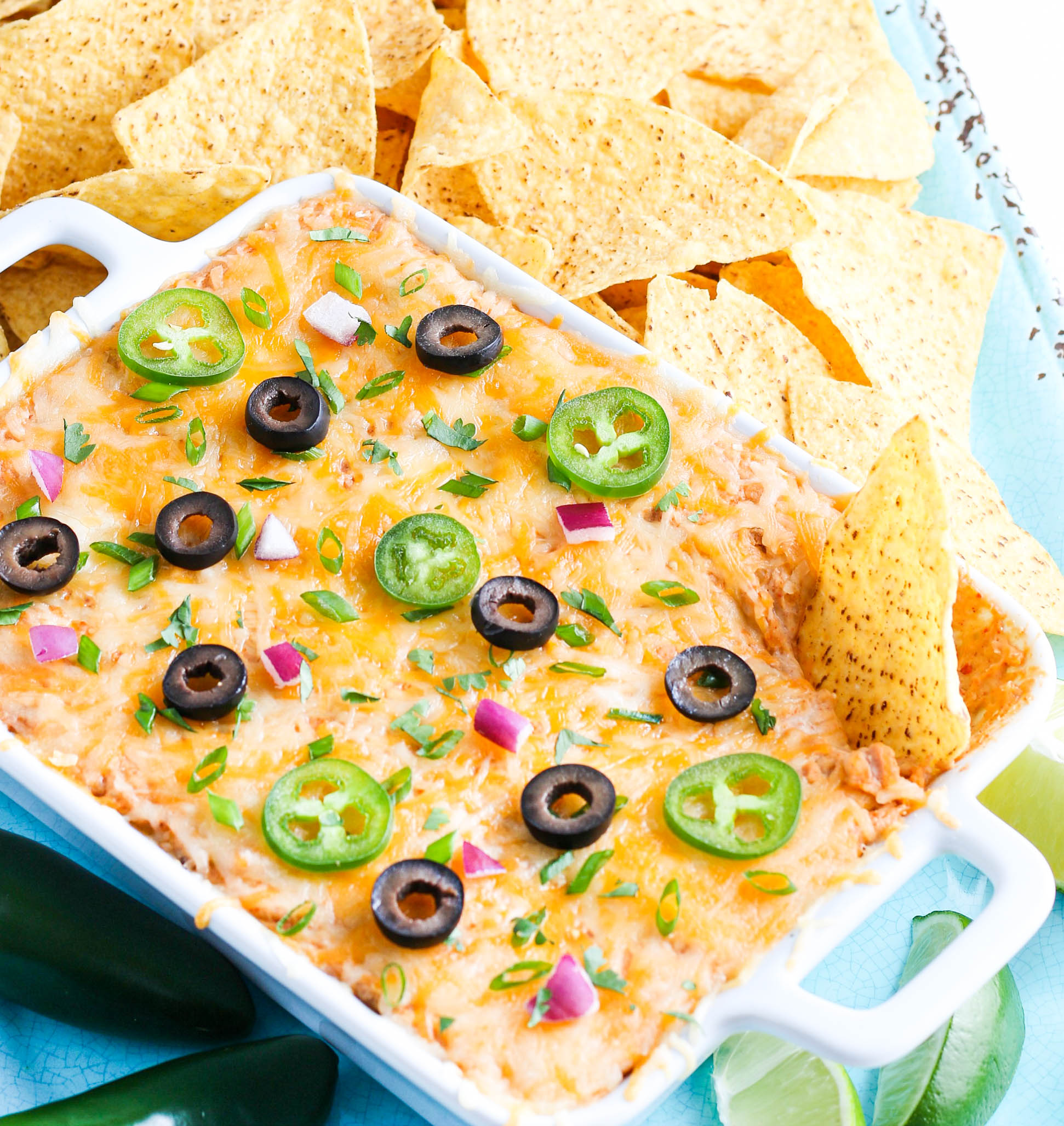 Easy Cheesy Bean dip in white baking dish with tortilla chips.