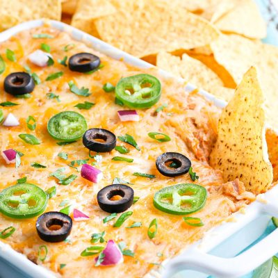 Easy Cheesy Bean Dip in white baking dish with tortilla chips