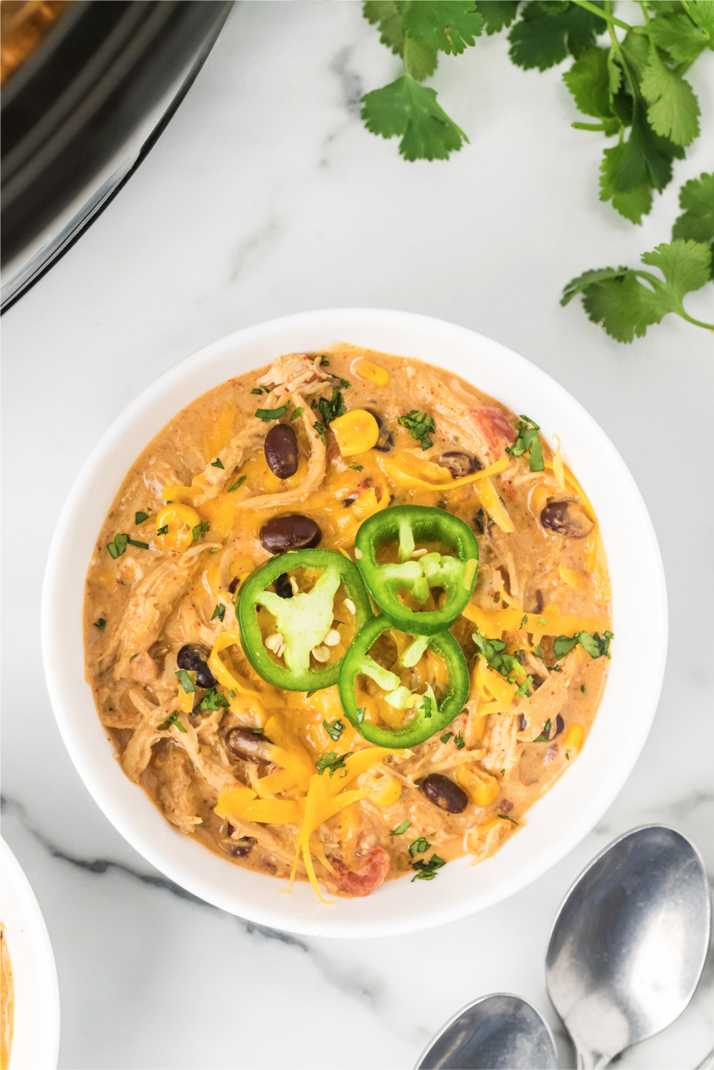 Ranch Chicken Chili recipe in white bowl with jalapenos and two spoons