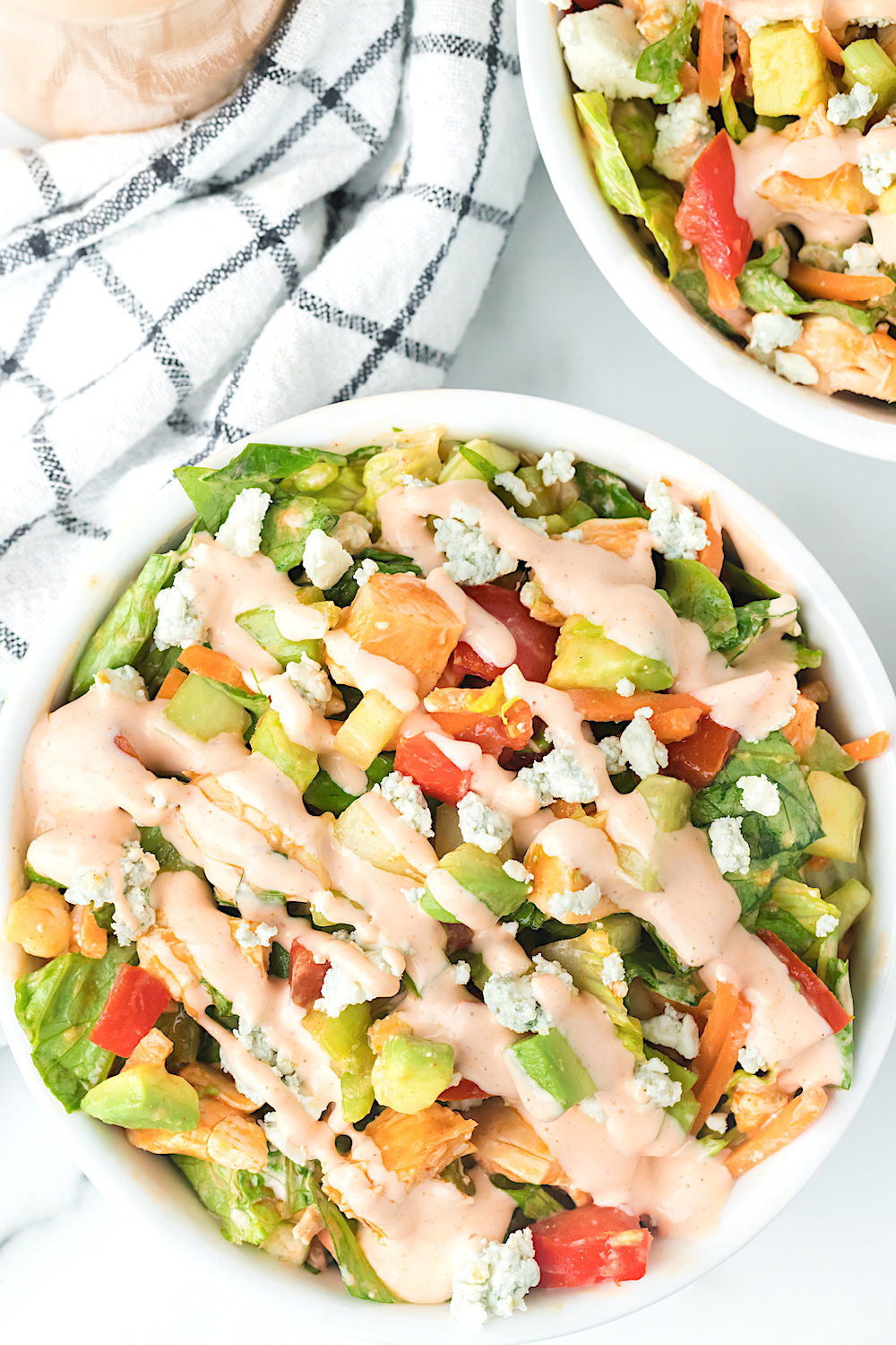 Buffalo Chicken Chopped Salad served in white bowls with dressing in mason jar on side.